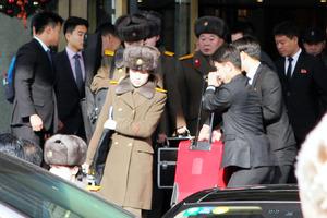 2015年12月12日、公演のキャンセルが決まり荷物を抱えて宿泊先のホテルを出る「モランボン楽団」のメンバーら=Imaginechina via AP Images)