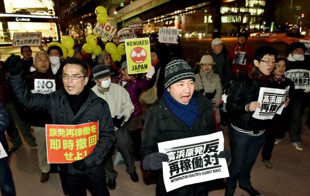 関西電力高浜原発の再稼働に反対し、関電東海支社前で抗議する人たち=25日夜、名古屋市東区、小川智撮影