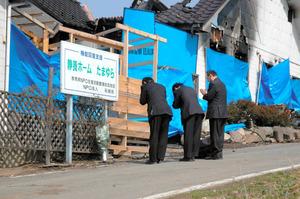 火災があった「静養ホームたまゆら」の前に献花し、手を合わせる東京都墨田区の職員たち=21日午後0時33分、群馬県渋川市、矢吹孝文撮影