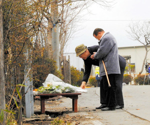 入所者の友人が焼け跡近くに設けられた献花台に花をたむけた=22日、群馬県渋川市