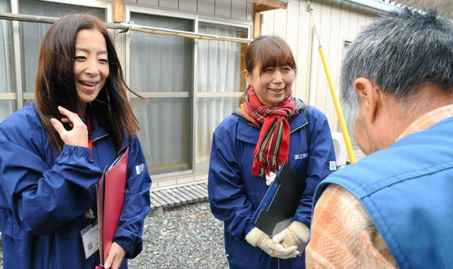 仮設住宅に避難する男性の話を聞く生活支援相談員の田中由起子さん(左)と新田かつえさん。今年最後の訪問で「よいお年を」とあいさつした=25日、福島県本宮市