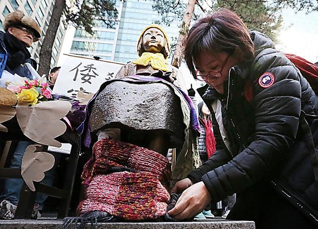 30日、ソウル市内の在韓日本大使館そばに設置された少女像の足にマフラーを巻く市民=東亜日報提供
