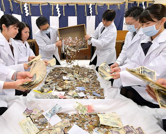 <繁盛祈願> 商売繁盛の神で知られる伏見稲荷大社(京都市伏見区)で4日朝、正月三が日のさい銭を集計する「さい銭開き」が始まった。社務所に集められたさい銭を、白衣姿の銀行員8人が手際よく数えていった。小切手、米ドルや中国・元などの外国紙幣も見られた