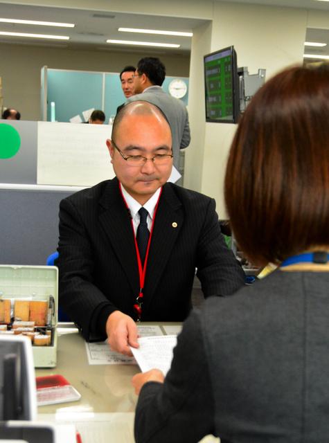 手続きを実演する大橋将人副会長(中央)=新潟市中央区