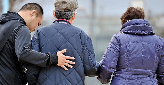 鍼灸(しんきゅう)マッサージ師(左)と妻(右)の介助を受けながら、暮らしているグループホーム近くの公園を歩く男性=大阪市、仙波理撮影