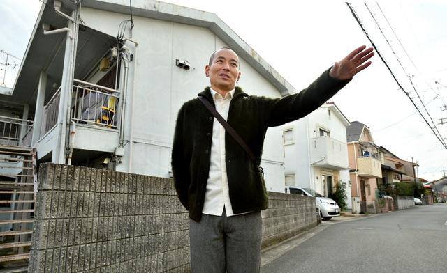 杉田真一さん。帰省してふるさとを歩いた。震災で残ったアパートと震災後の家が入り交じっていた=7日午後、兵庫県伊丹市、水野義則撮影