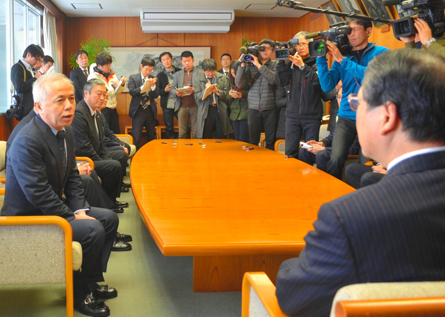 会田洋市長(右手前)にケーブル問題などについて陳謝する広瀬直己社長(左)=柏崎市役所