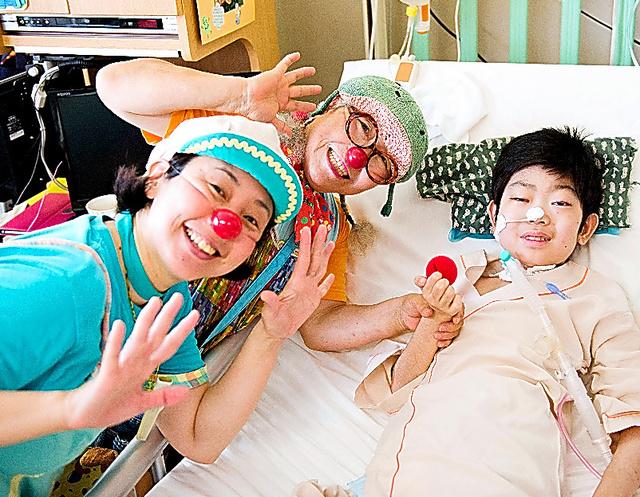 東北大学病院で子どもとふれあう山田ゆかりさん(左)=仙台市青葉区、日本クリニクラウン協会提供