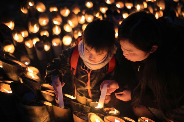 幼なじみを震災で亡くした神戸市中央区の平島智恵さん(36)はおいっ子の小野光琉くん(7)を連れて慰霊に訪れた。「教科書だけではわからない、大切な人を失うつらさや生きる大変さを伝えたい」=17日午前6時50分、神戸市中央区、内田光撮影