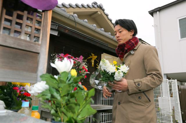 亡くなった母親の形見のマフラーを巻き、母子寮跡にできたほこらに花を捧げる鈴木佑一さん=17日午後、神戸市兵庫区、橋本弦撮影