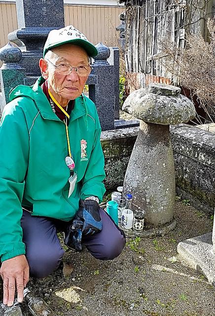 「いまでも観光客が訪れます」とボランティアガイドの佐藤善昭さん。とっくり形の墓(右)には酒が供えられていた=福島県白河市大工町の皇徳寺