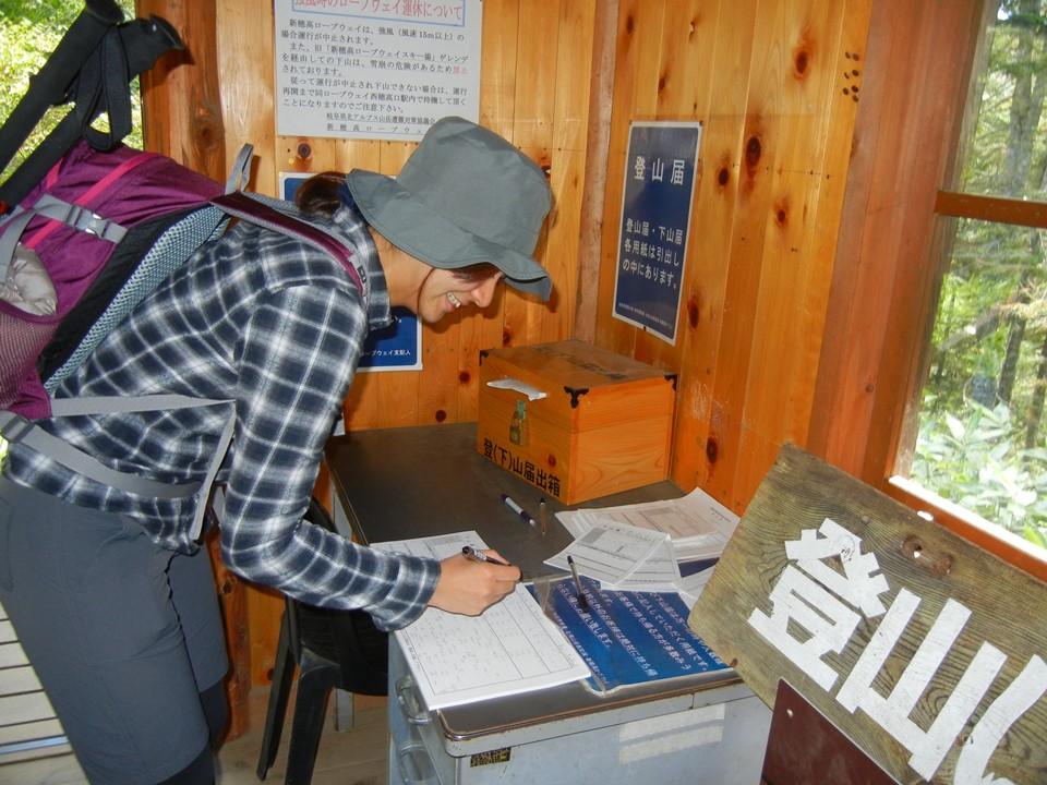新穂高ロープウェイ山頂駅近くの小屋で登山届を提出する女性登山者