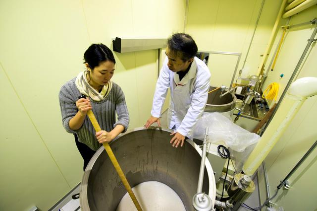 仕込みタンクの中に櫂(かい)を押し込んだ後、手前に引くようにして混ぜる(左が記者)=会津若松市