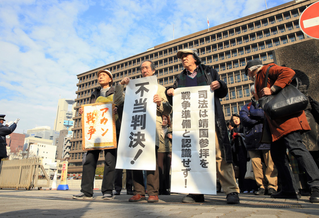 「不当判決」の旗の横で、請求棄却について抗議する原告ら=28日午前10時21分、大阪市北区、内田光撮影