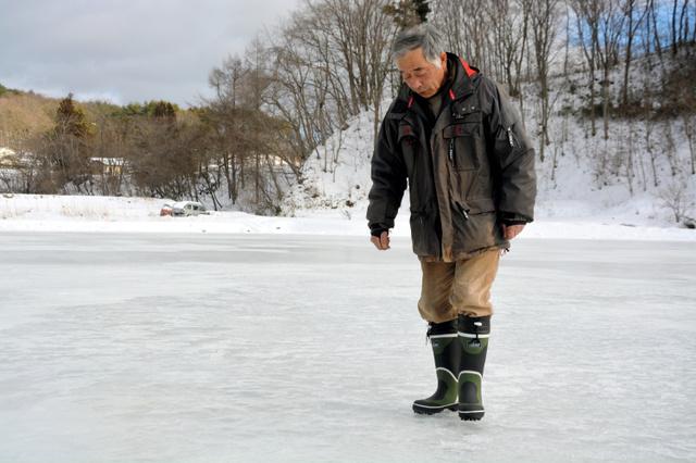 足でリンクを踏んで氷の張り具合を確かめる大内秀一さん=川俣町山木屋地区