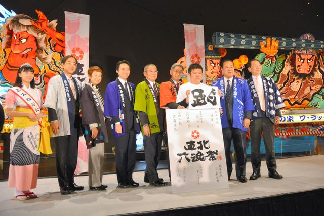 テーマの「跳(はねる)」の文字を掲げ、鹿内博・青森市長(右から4人目)をはじめ、東北6県の県庁所在地の市長らが並んだ=青森市