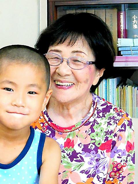 「北海道ノーモア・ヒバクシャ会館」で見学の児童と笑顔で記念撮影する越智晴子さん=2014年8月3日、札幌市白石区、北海道被爆者協会提供
