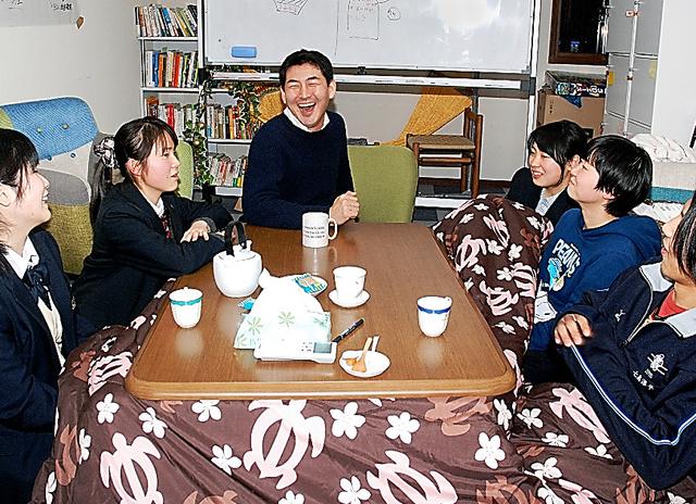 「次はどんなプロジェクトをしようか」。下校途中に事務所に立ち寄った生徒たちと話し合う伴場賢一さん(中央)=福島市五月町