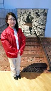 奥に寺山修司の写真がある。「青森駅から延びていた貨物線で撮ったそうです」と学芸員の広瀬有紀さん=青森県三沢市の「市寺山修司記念館」