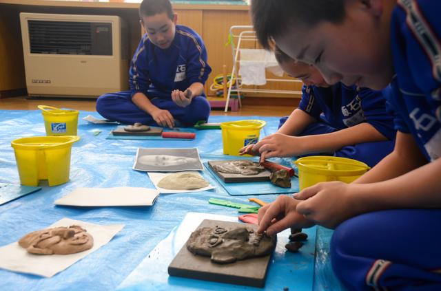 粘土で自分の顔をつくる児童たち=雲南市三刀屋町多久和