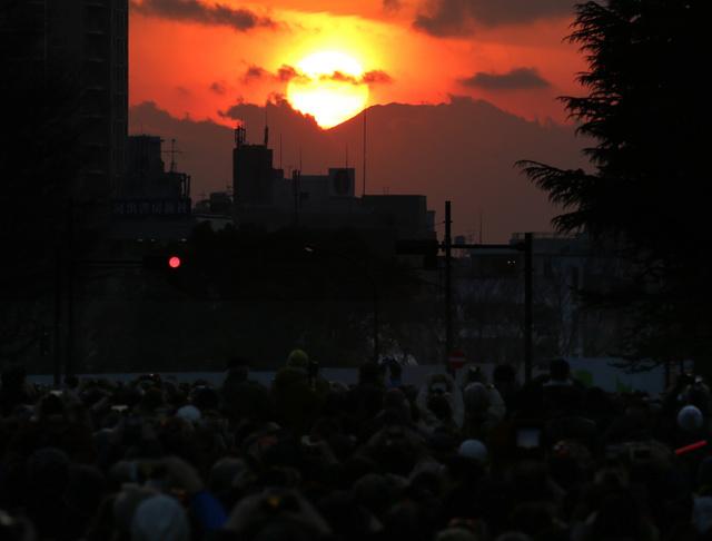 大勢の人が見守る中、富士山の頂上付近に沈む夕日=4日午後4時57分、東京都新宿区の神宮外苑、嶋田達也撮影