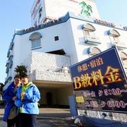 ラブホテルから模様替えしたホテルを背景に記念撮影する中国人観光客ら=5日午前、愛知県稲沢市、細川卓撮影