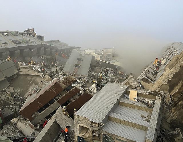 台湾・台南で6日、地震で倒壊した17階建てのマンションで救助活動をする隊員たち=ロイター