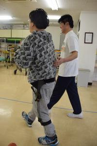 理学療法士(右)に付き添われ、左足にアクシブをつけて歩く男性=山口県下関市汐入町の昭和病院