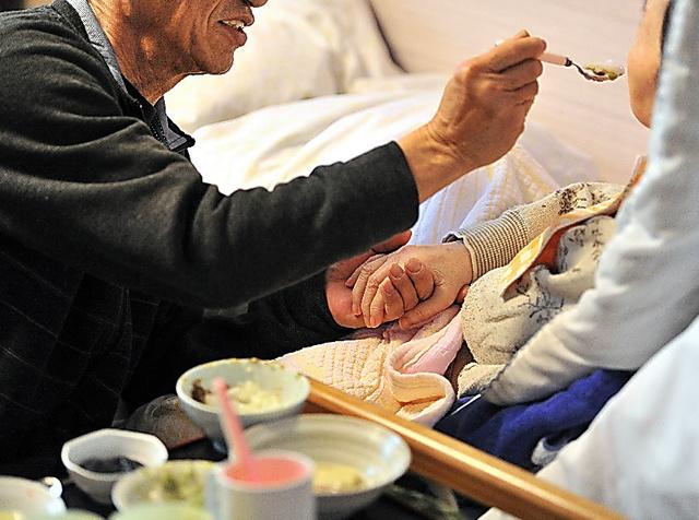 特別養護老人ホームで暮らす妻の口元に、食事を運ぶ男性。左手は、妻の手を握っていた=京都府内、仙波理撮影