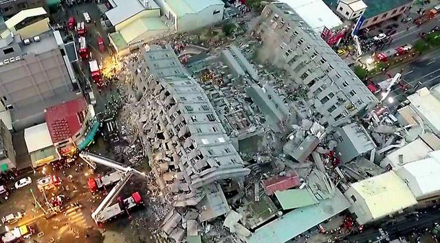台南で6日、建物が倒壊した現場。台湾のテレビ局「中天電視」の映像から=AFP時事