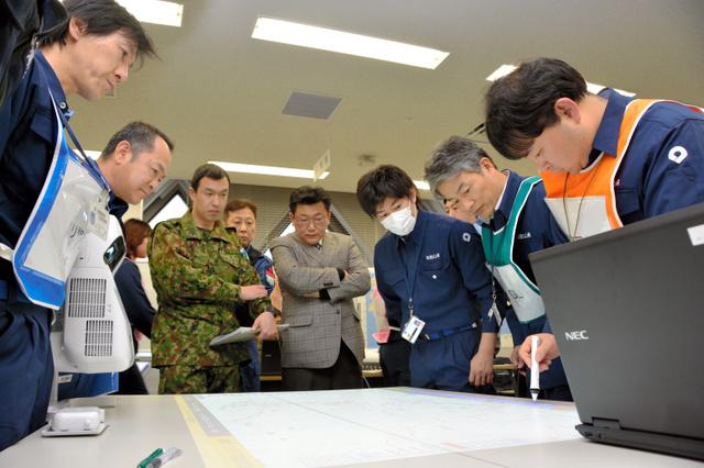机上に映し出された地図上で被災状況を共有する県庁や関係機関の職員ら=県庁