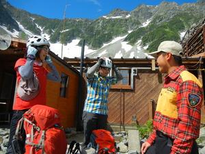 穂高連峰の登山基地の涸沢で、長野県警山岳遭難救助隊員(右)の「涸沢から着けてください」とのアドバイスでヘルメットを装着する登山者=2014年8月