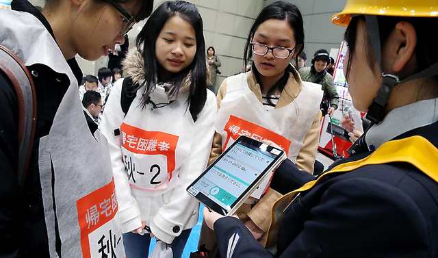 外国人の帰宅困難者には、タブレット端末の翻訳アプリを使って英語や中国語などで災害の情報などを伝えた=8日午前、東京・秋葉原、時津剛撮影