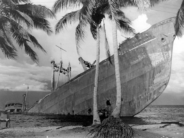 太平洋戦争の日米の激戦地・ガダルカナル島で海岸に乗り上げ、船体の半分が海中に没した日本の輸送船「九州丸」=米国立公文書館所蔵、全日本海員組合・戦没した船と海員の資料館提供