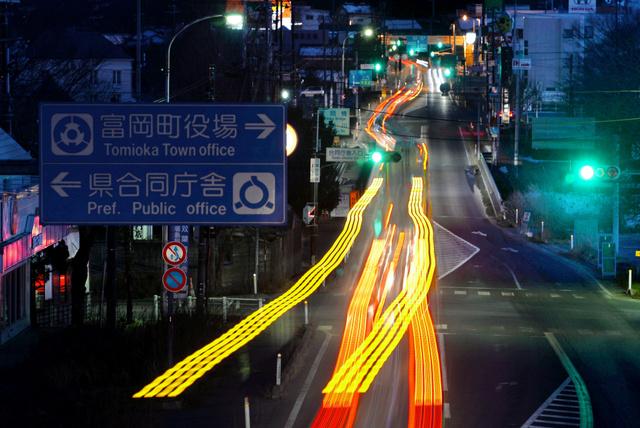 住民のいない福島県富岡町中心部の国道6号。夕方はいわき市方面へ向かう上り車線のみが混雑する=4日午後5時32分、長時間露光、福留庸友撮影