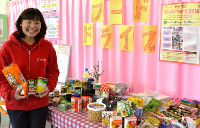 集まった食料品と店長の西山晴美さん=カーブス南生駒店