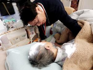 自宅で療養する岡田たけ子さんに声をかける新田国夫医師=2日、東京都国立市