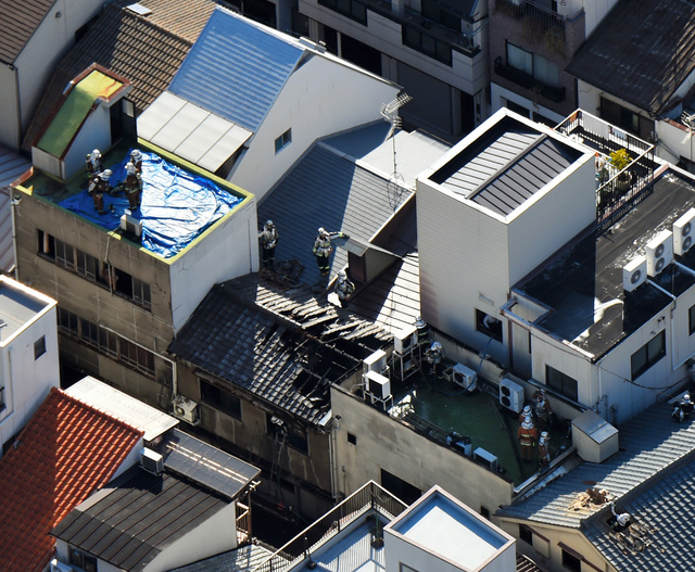 民家の屋上などで消火活動をする消防隊員=11日午後2時36分、大阪市北区、朝日新聞社ヘリから、井手さゆり撮影