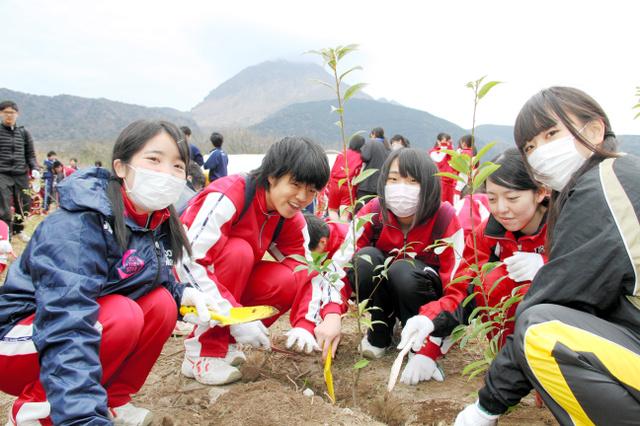 雲仙普賢岳を背に、思いを込めながら植樹する高校生たち=島原市