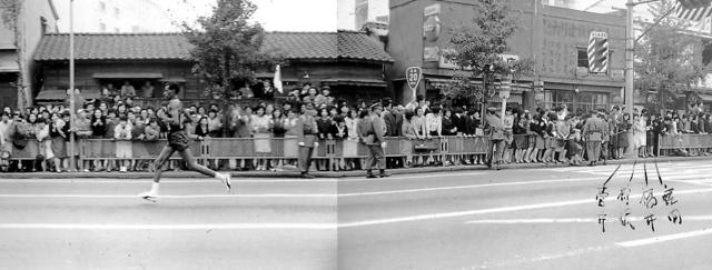 甲州街道を駆けるアベベ選手。写真には、仲間たちの名も書き込んであった。一番左の「菅井」が小池さんの旧姓だ=東京都渋谷区代々木、小池広美さん提供