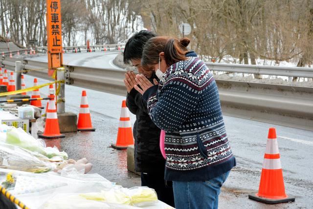 事故現場に設けられた献花台に目を閉じて手を合わせる夫婦=13日午前11時54分、長野県軽井沢町、辻隆徳撮影