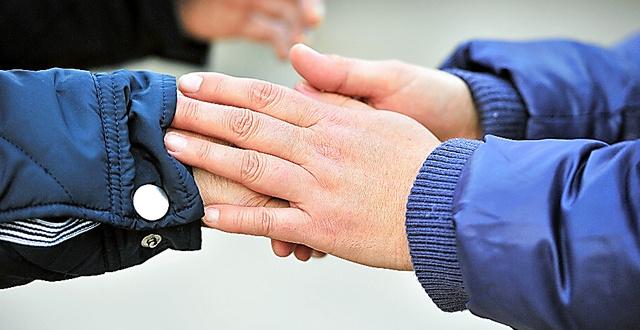 認知症の夫と公園を歩き、冷えた夫の手(左)をさする妻(1月10日に記事掲載)=大阪市内、仙波理撮影