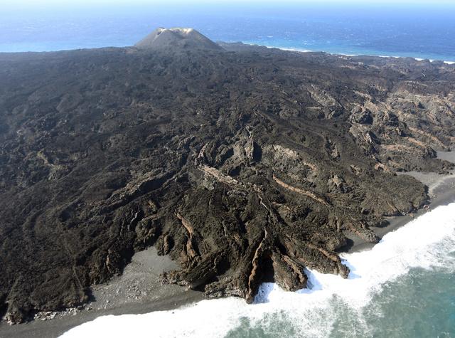 火山活動が落ち着いてきた西之島。奥に火口が見える=10日、太平洋の小笠原諸島、朝日新聞社機から、川村直子撮影