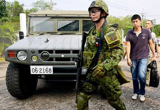 在外邦人の輸送訓練で、高機動車を降りて、小銃を持った陸上自衛隊員に警護されながら、空港へ向かう人たち=17日、タイ中部のウタパオ海軍航空基地、福井悠介撮影