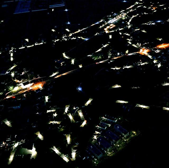 昨年9月に避難指示が解除された福島県楢葉町のJR常磐線の木戸駅(中央上)周辺。町内では民家が多い地域だが、住民が戻っていないため、街灯が照らす道だけが点線のように浮かびあがっていた。中央のオレンジ色の光跡は国道6号=1月13日、福島県楢葉町、本社ヘリから、福留庸友撮影