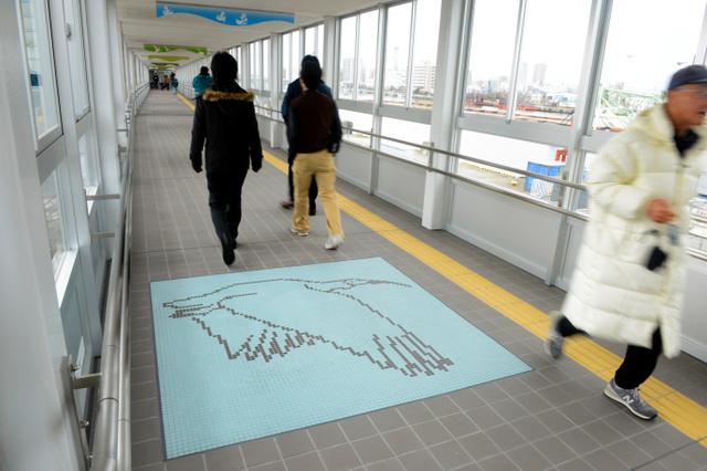 通路の床にはタイルでトキなどがあしらわれている=新潟市中央区万代島