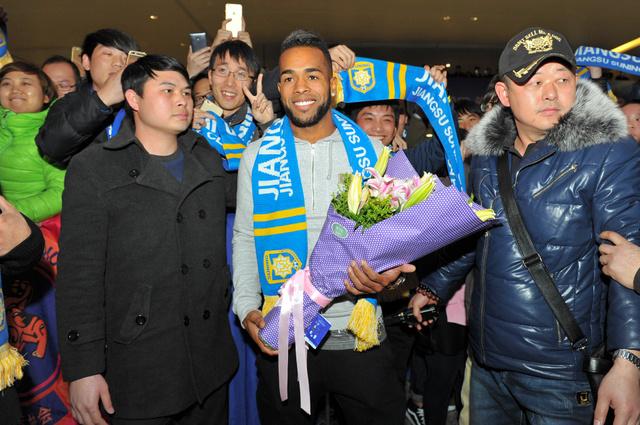 南京で13日、地元チーム江蘇蘇寧に加わるため空港に降り立ったブラジル人フォワードのテイシェイラ選手(中央)。今年最高の移籍額となった=AP