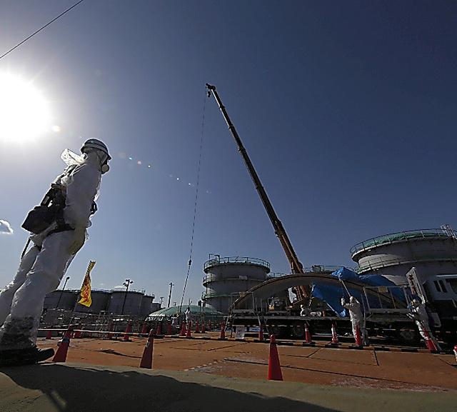 汚染水タンクの解体作業を進める作業員ら=19日午後、福島県大熊町、杉本康弘撮影