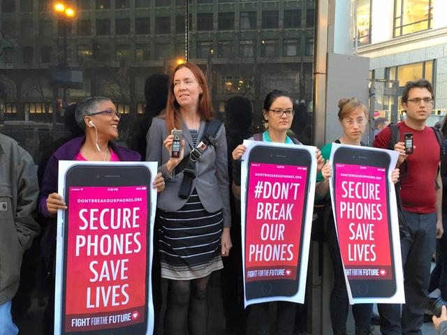 アップルストア前に集まり、「携帯を守れ」などと書いたポスターを持ってアップル支持を訴える人たち=サンフランシスコ、宮地ゆう撮影