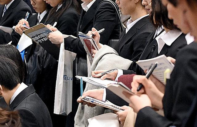 企業の合同説明会場で、聞いた内容を熱心にメモする学生=1日午前、千葉市美浜区、諫山卓弥撮影